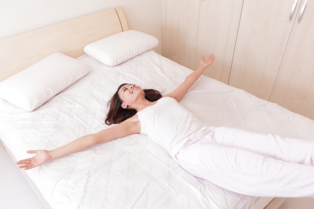 Bonne femme de s'allonger et de sauter sur son lit à la maison Banque d'images - 21088107