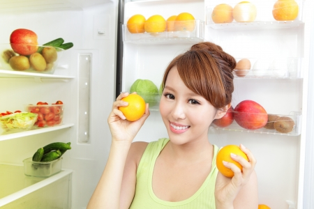 Healthy Eating Concept .Diet. Beautiful Young Woman near the Refrigerator with healthy food. Fruits and Vegetables, asian model photo