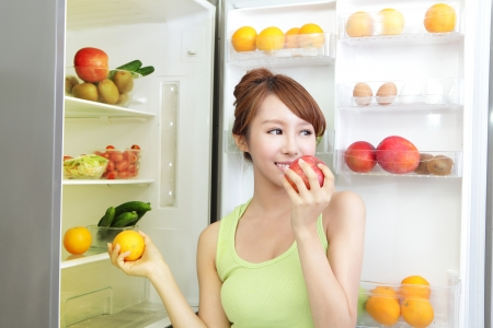 Healthy Eating Concept .Diet. Beautiful Young Woman near the Refrigerator with healthy food. Fruits and Vegetables, asian model Stock Photo - 21173938