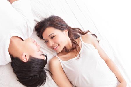 pareja durmiendo: encantadora pareja joven acostado en una cama, sonrisa feliz mirando el uno al otro, vista desde arriba, las personas asi�ticas Foto de archivo