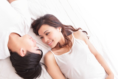 asian ladies: young lovely couple lying in a bed, happy smile looking to each other, top view, asian people