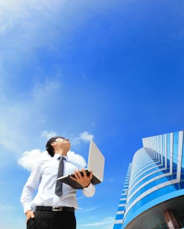 constat: Jeune homme d'affaires utilisant un ordinateur portable et de regarder vers le ciel bleu et de nuages ??avec le paysage urbain dans le concept d'informatique arri�re-plan, les entreprises et les nuages Banque d'images
