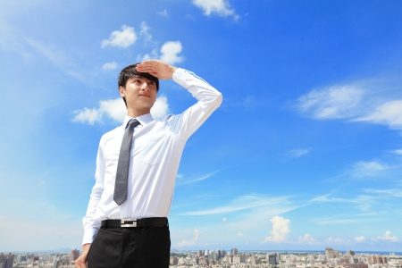 purpose: Successful handsome business man purposefully looking away with blue sky and city background, mode is a asian male Stock Photo