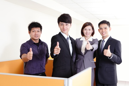 Portrait of happy business partners smiles and showing thumb up sign in office photo