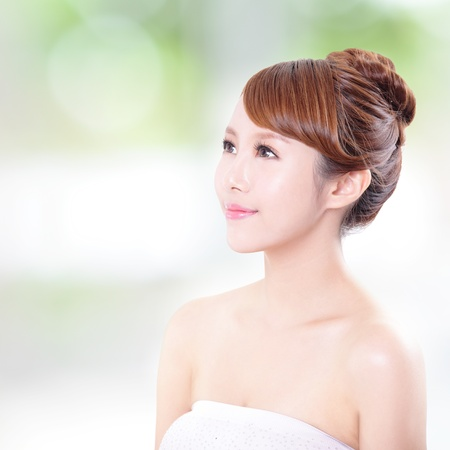 face side: portrait of the woman with beauty face and perfect skin, and she look to empty copy space,  isolated on green background, asian model