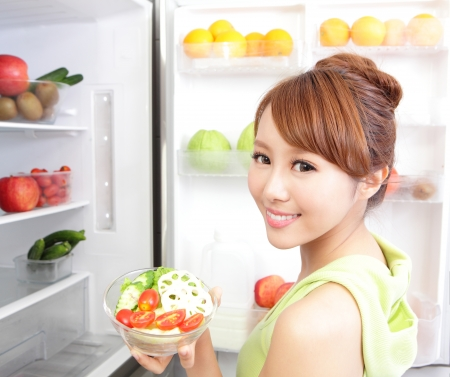 icebox: Healthy Eating Concept .Diet. Beautiful Young Woman near the Refrigerator with healthy salad, Fruits and Vegetables, asian model Stock Photo