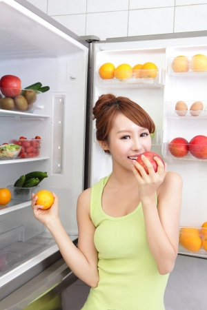 icebox: Healthy Eating Concept .Diet. Beautiful Young Woman near the Refrigerator with healthy food. Fruits and Vegetables, asian model