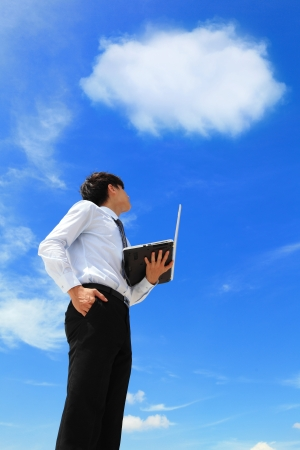 cloud computer: Young business man using laptop and look to blue sky and cloud with cityscape in the background, business and cloud computing concept