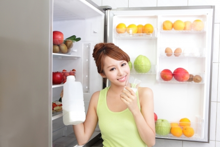 icebox: Healthy Eating Concept .Diet. Beautiful Young Woman drink milk near the Refrigerator. Fruits and Vegetables, asian model Stock Photo