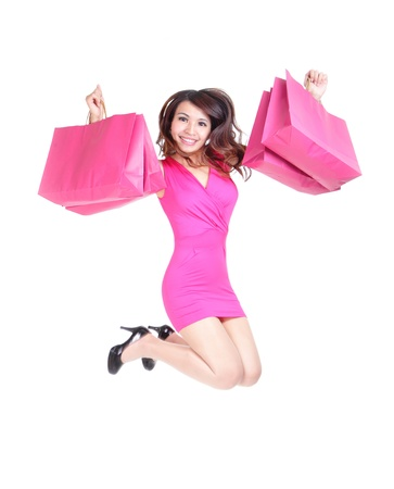 happy shopping young woman jumping with color bags - isolated on white background, full body, asian model photo