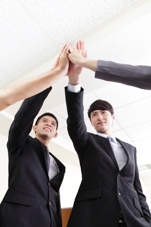 Successful business people group celebrating with hands giving high five at office, asian people photo