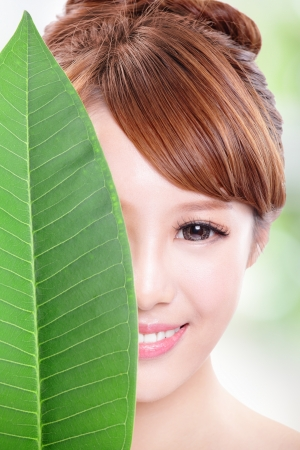 close up of beautiful woman face portrait with green leaf , concept for skin care or organic cosmetics , asian beauty model photo