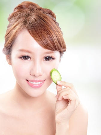 Portrait of young beautiful woman holding cucumber slices on her face, concept for skin care, asian model Stock Photo - 21378576