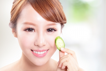 Portrait of young beautiful woman holding cucumber slices on her face, concept for skin care, asian model photo