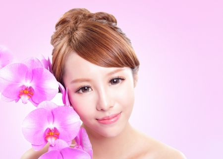 Beautiful woman smile face with orchid flowers and health skin isolated on pink background, asian model