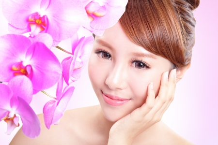 Beautiful woman smile face with orchid flowers and health skin isolated on pink background, asian model photo