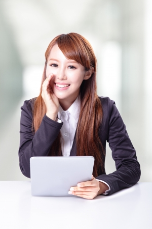 business woman talking and using tablet computer pc in office, model is a asian woman