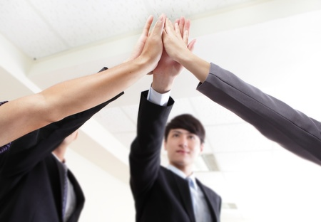 Successful business people group celebrating with hands giving high five at office,focus on hans, asian people