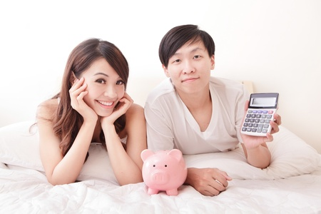 family budget: young happy couple lying in a bed with pink piggy bank and calculator, asian family
