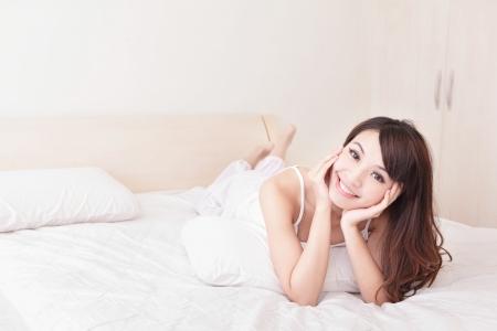 mujer en la cama: Primer plano de una mujer joven y feliz sonrisa mientras est� acostado en la cama en su casa, el modelo es una chica asi�tica