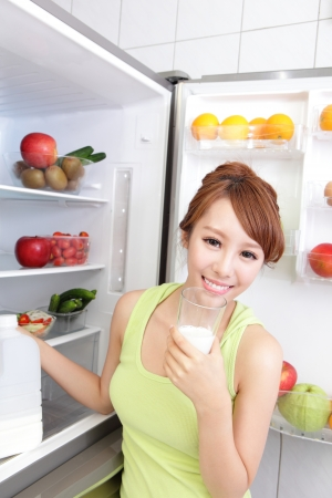 Healthy Eating Concept .Diet. Beautiful Young Woman drink milk near the Refrigerator. Fruits and Vegetables, asian model photo