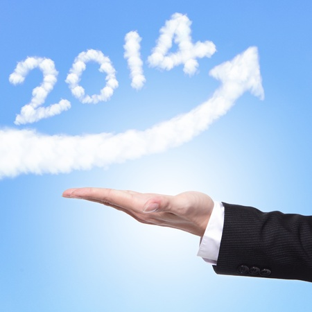hand of Business man holding happy new year 2014 (white cloud and blue sky on sunny day) on his hand photo