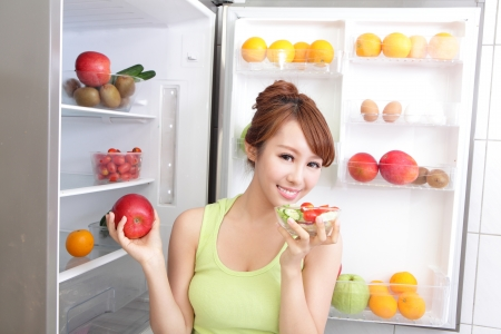 Healthy Eating Concept .Diet. Beautiful Young Woman near the Refrigerator with healthy food. Fruits and Vegetables, asian model Stock Photo - 21436920