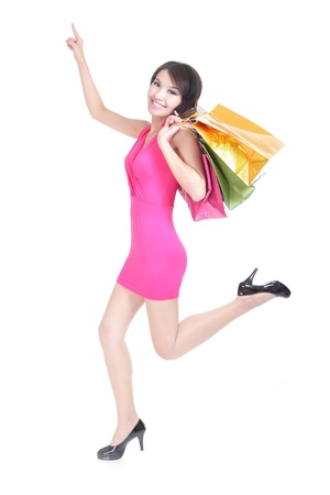 asian shopper: happy shopping young woman running and finger point to copy space with bags - isolated on white background, full body, asian model