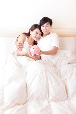 young happy couple lying in a bed with pink piggy bank, asian family photo