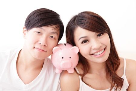 asian wedding: young happy couple lying in a bed with pink piggy bank, asian family