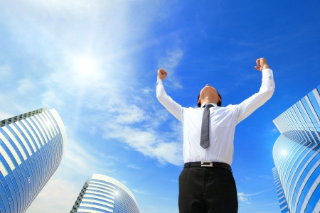 happy successful business man raised arms with sky in the background, asian people photo