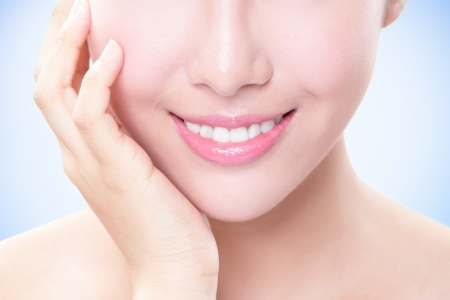 Beautiful young woman teeth close up with hand. Isolated over blue background, asian beauty model photo