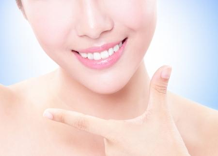 dentista: Joven y bella mujer dientes de cerca con la mano. Aislado sobre fondo azul, modelo de belleza asi�tica