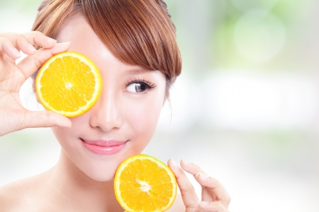 Beautiful woman face with juicy orange and look empty copy space, green background, asian beauty model photo