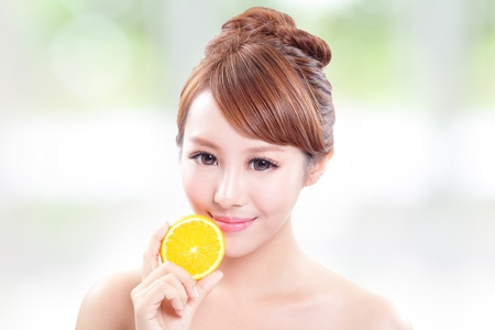asian woman face: Beautiful woman face with juicy orange, green background, asian beauty model