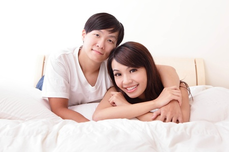 young lovely couple lying in a bed, happy smile face, asian people photo