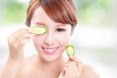 eye cream: Portrait of young beautiful woman holding cucumber slices on her face, concept for skin care, asian model