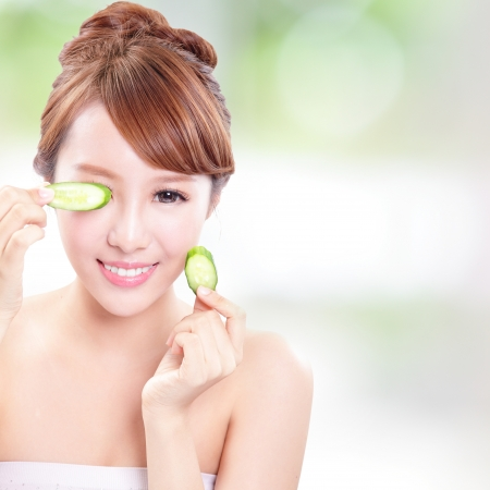 Portrait of young beautiful woman holding cucumber slices on her face, concept for skin care, asian model