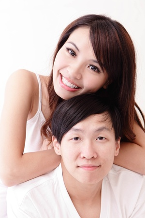 man woman hugging: young lovely couple lying in a bed, happy smile looking to camera, asian people