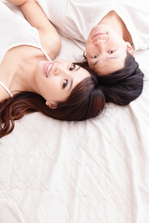young lovely couple lying in a bed, happy smile looking to camera, top view, asian people photo