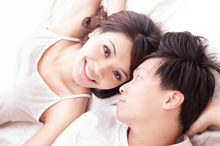 portrait couple: young lovely couple lying in a bed, happy smile looking to each other, top view, asian people