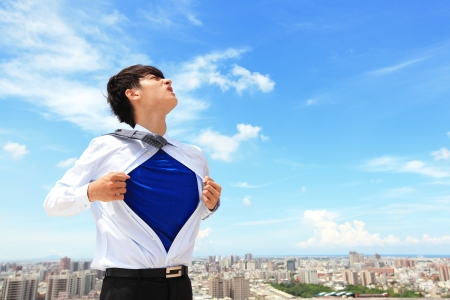 Business man pulling his t-shirt open, showing a superhero suit underneath his suit, with city background photo