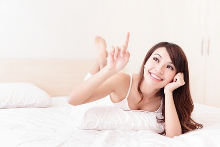 asian home: Close up of a happy young woman smile and look to empty copy space while lying on the bed at home , model is a asian girl