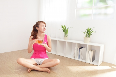 asian flavors: Beautiful Young Woman drinking hot tea at home with wood floor in the morning, healthy lifestyle concept, asian beauty