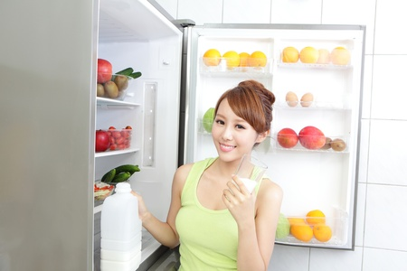 refrigerator with food: Healthy Eating Concept .Diet. Beautiful Young Woman drink milk near the Refrigerator. Fruits and Vegetables, asian model Stock Photo