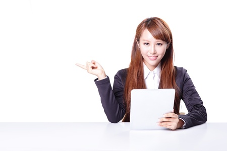 business woman show copy space with tablet pc in office, model is a asian woman photo