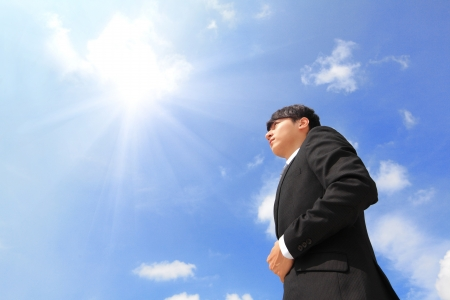 Successful business man standing over blue sky and purposefully looking away. photo