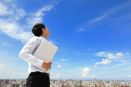 cloud computing concept: Young business man using laptop and look to blue sky and cloud with cityscape in the background, business and cloud computing concept