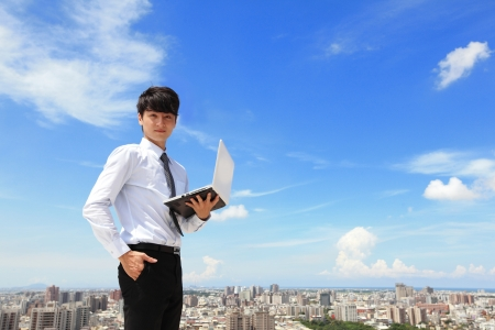 Young business man using laptop and look to you with cityscape in the background, business and cloud computing concept