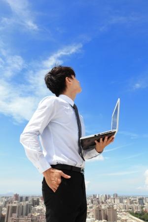 közlés: Fiatal üzletember használ laptop, és nézd, hogy a kék ég és a felhő városkép a háttérben, az üzleti és a számítási felhő koncepciója